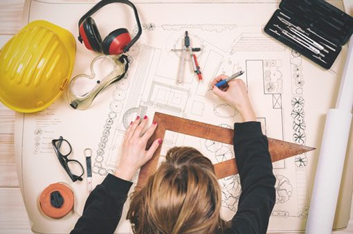 Woman working on architectural plans.