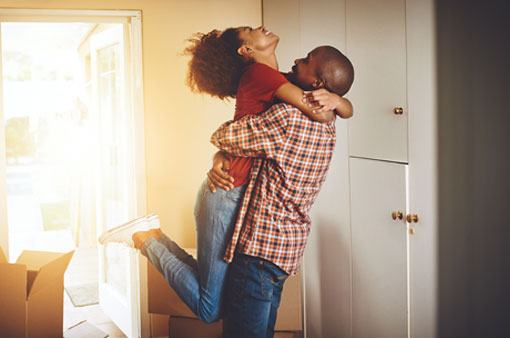 Couple embracing in their new home.